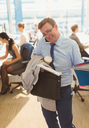 Stressed businessman struggling to multitask in office - CAIF06659