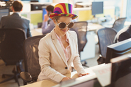 Playful businesswoman wearing silly sunglasses and striped hat at computer in office - CAIF06662