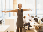 Exuberant businesswoman celebrating with arms outstretched on top of chair in office - CAIF06674