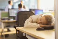 Businesswoman sleeping on desk in office - CAIF06680