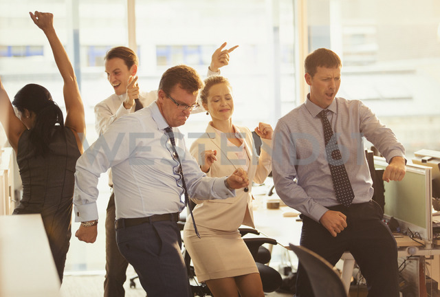 Enthusiastic business people celebrating and dancing in office - CAIF06683 - Paul Bradbury/Westend61