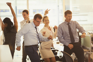 Enthusiastic business people celebrating and dancing in office - CAIF06683
