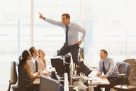 Laughing colleagues watching exuberant businessman dancing on top of desks in office - CAIF06686