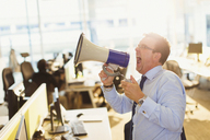 Exuberant businessman shouting into megaphone in office - CAIF06689