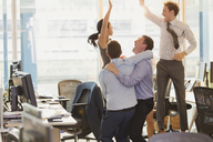 Exuberant business people celebrating and jumping in office - CAIF06695