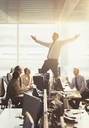 Colleagues watching exuberant businessman celebrating on top of desks in office - CAIF06701
