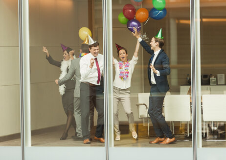Business people wearing party hats and dancing with balloons at conference room window - CAIF06707