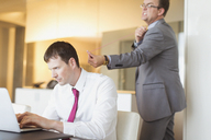 Angry businessman aiming rubber band at unsuspecting businessman working at laptop - CAIF06713