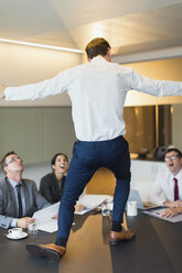 Surprised colleagues watching exuberant businessman dancing on conference table - CAIF06716