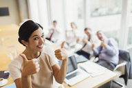 Portrait confident businesswoman and colleagues gesturing thumbs-up in conference room - CAIF06719