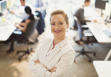 Portrait of confident businesswoman with arms crossed in office - CAIF06725