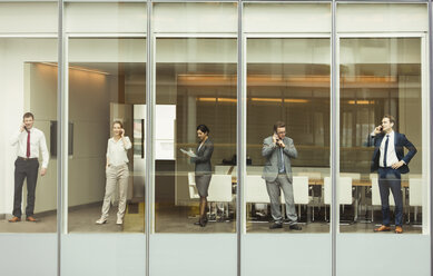 Business people talking on cell phones and reviewing paperwork at conference room window - CAIF06731