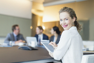 Portrait smiling businesswoman using digital tablet in conference room meeting - CAIF06734