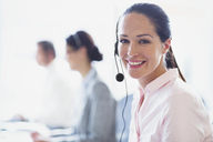Portrait of smiling businesswoman talking on the phone with headset - CAIF06770