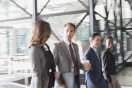 Corporate business people talking and entering modern office lobby - CAIF06785