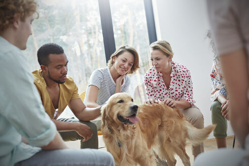 People petting dog in group therapy session - CAIF06842