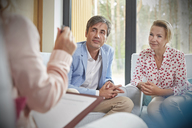 Couple listening to therapist in couples therapy counseling session - CAIF06854
