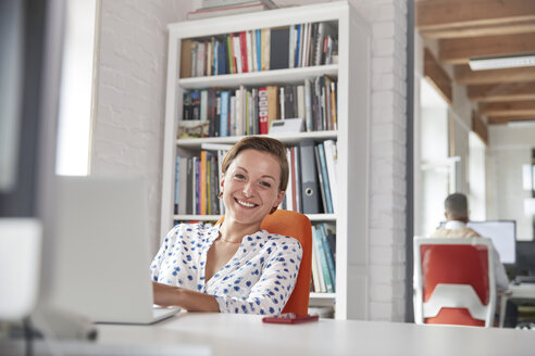 Portrait smiling, confident businesswoman working at laptop in office - CAIF06887