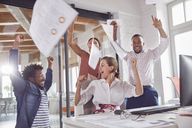 Exuberant business people celebrating, throwing paperwork overhead in office - CAIF06899