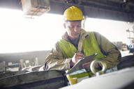 Steelworker writing on clipboard in steel mill - CAIF06932