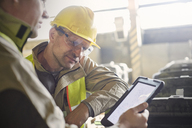 Steelworkers using digital tablet in steel mill - CAIF06944