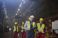Supervisor and steelworkers walking and talking in steel mill - CAIF06950