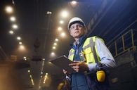 Serious steelworker supervisor with clipboard in steel mill - CAIF06956