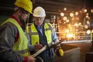 Supervisor and steelworker with clipboard talking in steel mill - CAIF06959