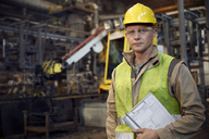 Portrait serious, confident steelworker with clipboard in steel mill - CAIF06980