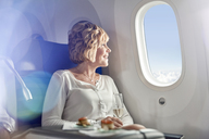 Smiling woman drinking champagne, traveling first class, looking out airplane window - CAIF06983