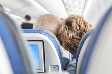 Rear view affectionate mature couple leaning on airplane - CAIF06989