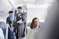 Flight attendant helping businessman with boarding pass on airplane - CAIF06995