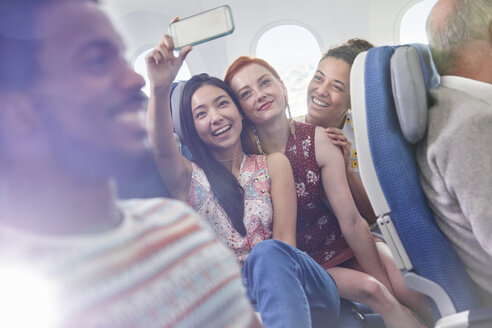 Young women friends with camera phone taking selfie on airplane - CAIF06998