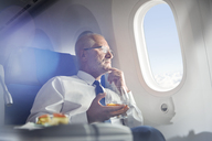Senior businessman drinking whiskey in first class, looking out airplane window - CAIF07001