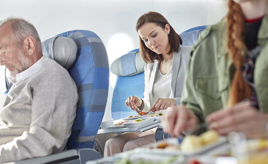 Woman eating dinner on airplane - CAIF07004