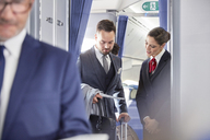 Flight attendant helping businessman with boarding pass on airplane - CAIF07019