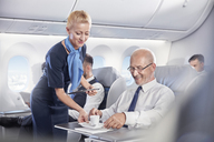 Flight attendant serving espresso coffee to businessman in first class on airplane - CAIF07028