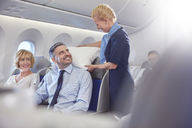 Smiling flight attendant adjusting pillow for businessman in first class on airplane - CAIF07049