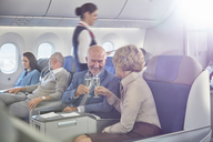 Mature couple toasting champagne glasses in first class on airplane - CAIF07052