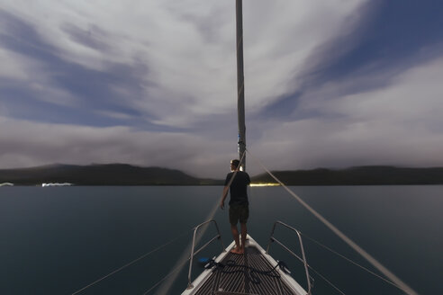 Indonesia, Lombok island, man on deck of a sailing boat at dusk - KNTF01082