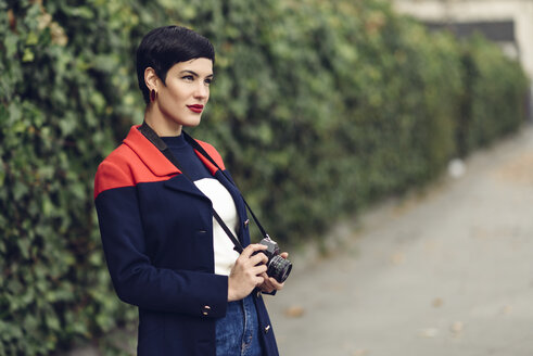 Portrait of fashionable young woman with camera - JSMF00083