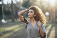 Portrait of young woman in a park at evening twilight - JSMF00096