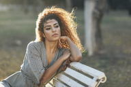 Portrait of pensive young woman relaxing on bench in a park at sunset - JSMF00102
