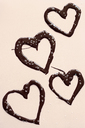 Chocolate hearts and confetti on light background - HSTF00059