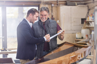 Male customer signing paperwork for finished wood kayak in workshop - CAIF07061