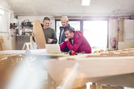 Male carpenters using laptop near wood boat in workshop - CAIF07067