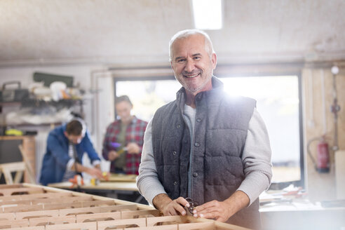 Portrait smiling male carpenter working on wood boat in workshop - CAIF07070