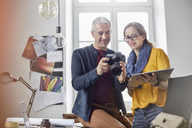 Photographers using digital tablet and digital camera in office - CAIF07091