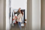 Painters examining painting in art studio - CAIF07094