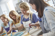 Female artists painting picture frames in art class workshop - CAIF07133